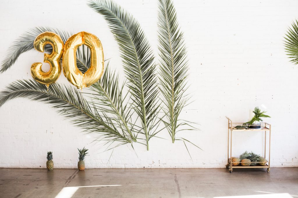 tropical theme 30th birthday chic party ideas backdrop palm leaves branches